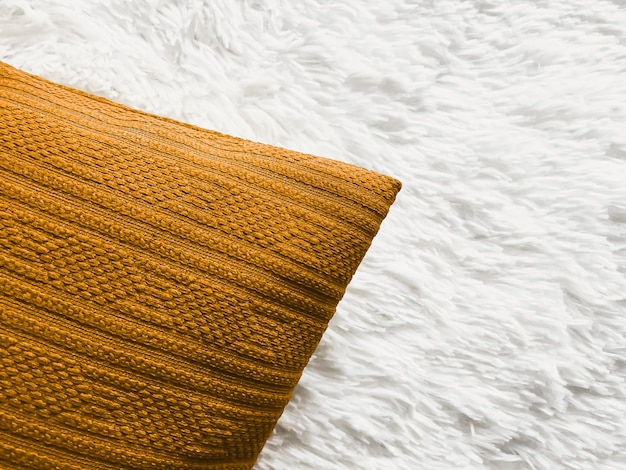 Golden cushion throw pillow on white fluffy plaid blanket as flat lay background bedroom top view an...