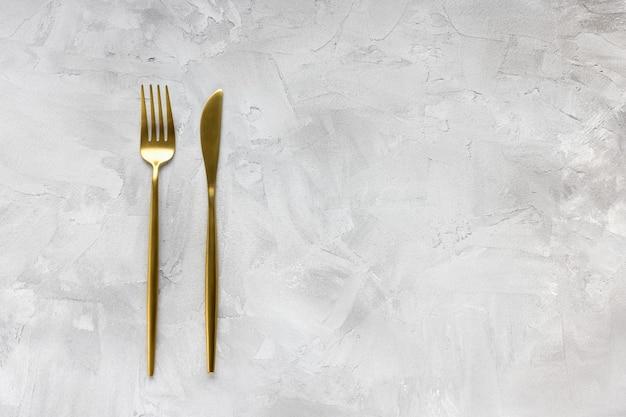 황금 칼 붙이 포크와 나이프와 황금 호 일 별 시안 색 배경에 색종이. 휴일 요리, 식사, 축하 및 음식 개념. 평면도, 클로즈업, 평평하다, 복사 공간