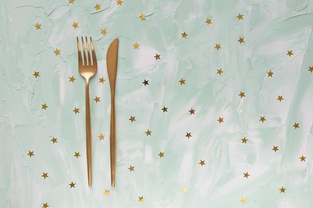 Золотые столовые приборы вилка и нож и золотая фольга звезды конфетти на зеленом столе.