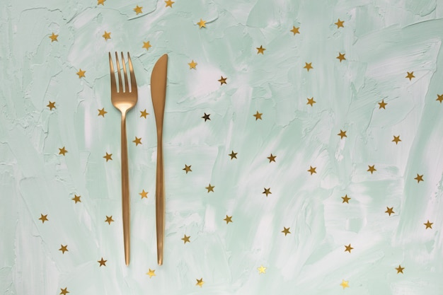 Golden cutlery fork and knife and golden foil stars confetti on green table.