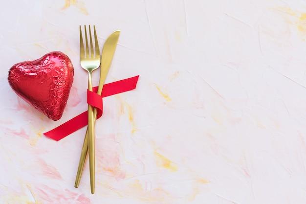 Золотые столовые приборы в красной ленте и шоколадное сердце в красной фольге на розовом