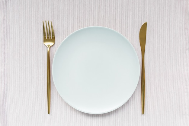 Golden cutlery and plate on pink background
