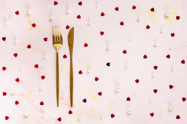 Golden cutlery and red foil hearts confetti and white pearls decoration on pink background. valentines day concept