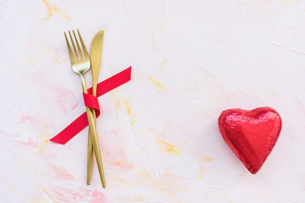 Golden cutlery in red ribbon and heart on pink