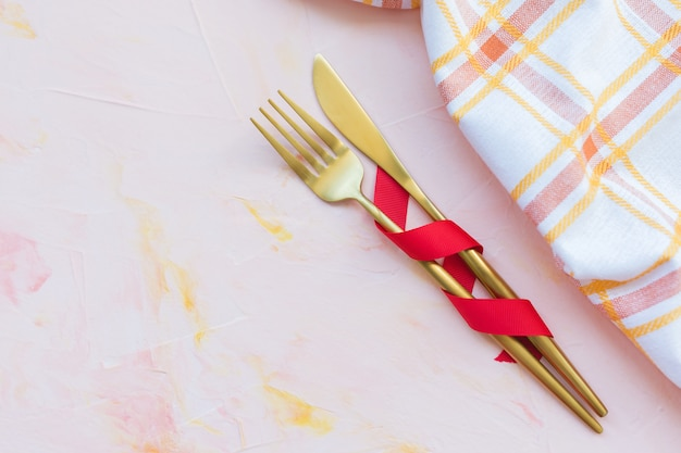 Golden cutlery in red ribbon and kitchen towel on a pink background