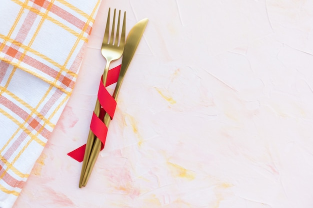 Golden cutlery in red ribbon and kitchen towel on a pink