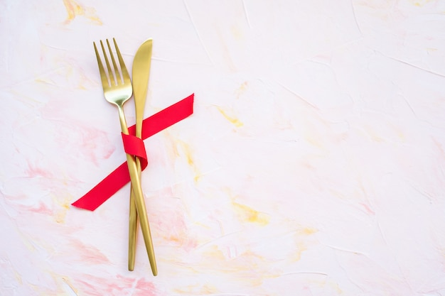 Golden cutlery in red ribbon on a pink background