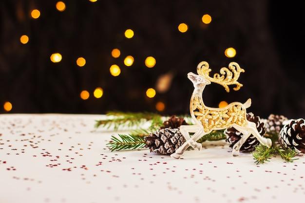 Золотой олень и сосновые шишки лежат на белом фоне за боке на темном фоне