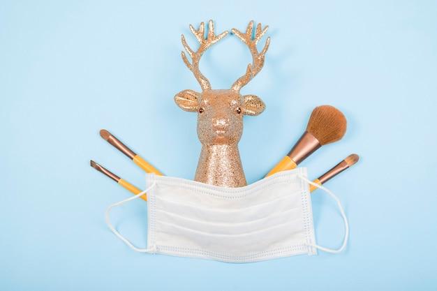 Голова золотого оленя с медицинской маской, косметические кисти на синем фоне