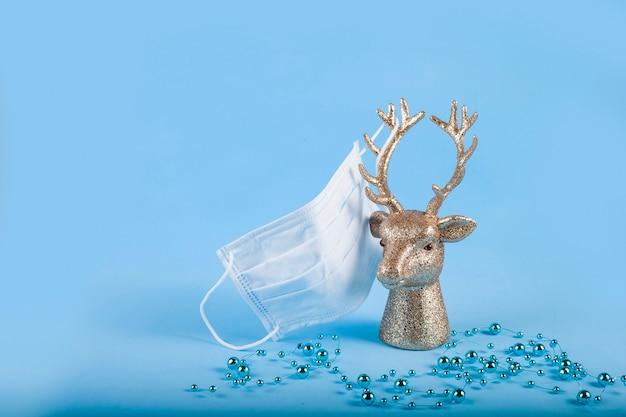 Голова золотого оленя с медицинской маской на рогах на синем фоне