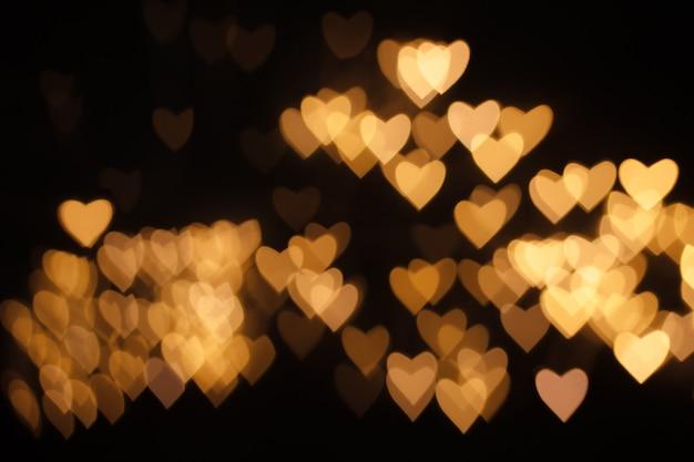 Golden defocus lights in the shape of hearts on black background