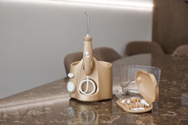 Спринклерный ирригатор golden dentist стоит на столе на ярко-белой поверхности с открытой крышкой, вид сверху, внутри различные насадки