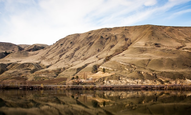 Golden desert canyon with reflection in river beneath