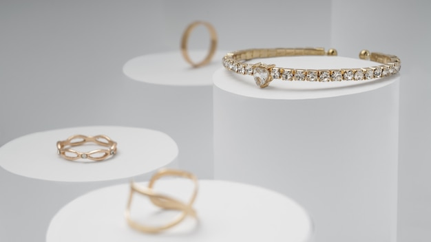 Golden and diamonds bracelet and golden rings on white display