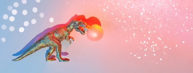 Golden dinosaur inflates bubble gum, concept with shadow