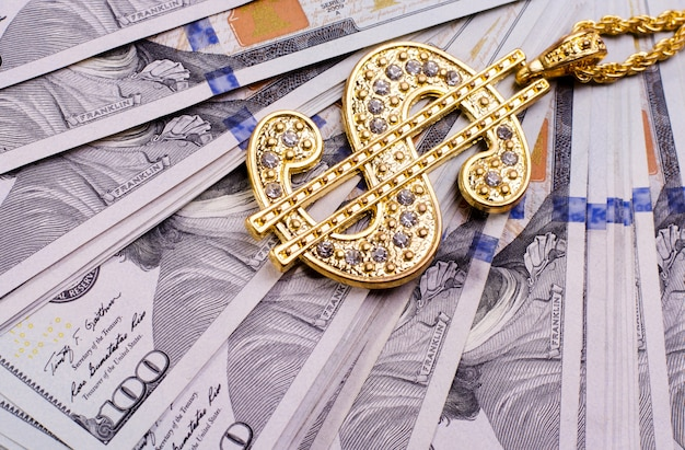 Golden dollar sign necklace on a us dollars banknotes
