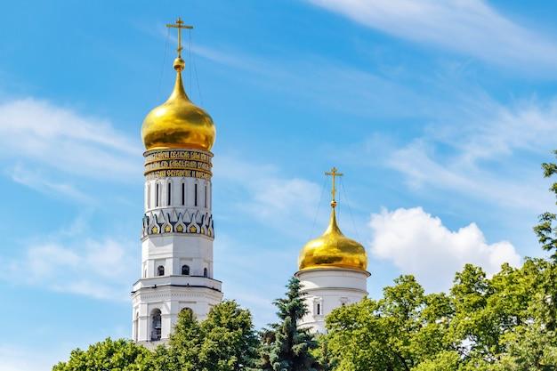 Золотые купола колокольни ивана великого и успенской колокольни на фоне голубого неба с белыми облаками и зелеными деревьями в солнечном свете