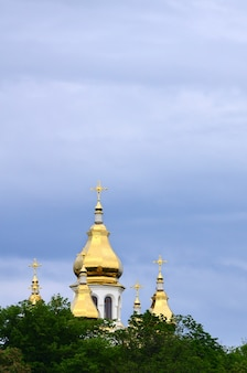 Golden domes of an orthodox church among blossoming trees against a background of a cloudy blue sky