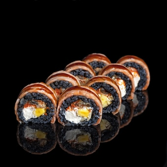 Golden dragon sushi roll. sushi rolls with black rice, salmon, mango with reflection on black background. close up. japanese cuisine. photo for menu