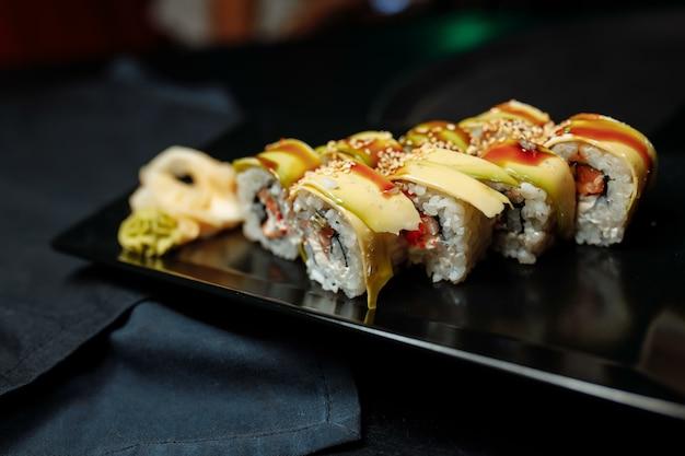 マグロ、きゅうり、ごま、とびこキャビアを添えたゴールデンドラゴン巻き寿司。