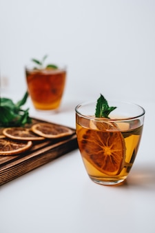 Golden drink, iced tea with a ring of dried orange and mint