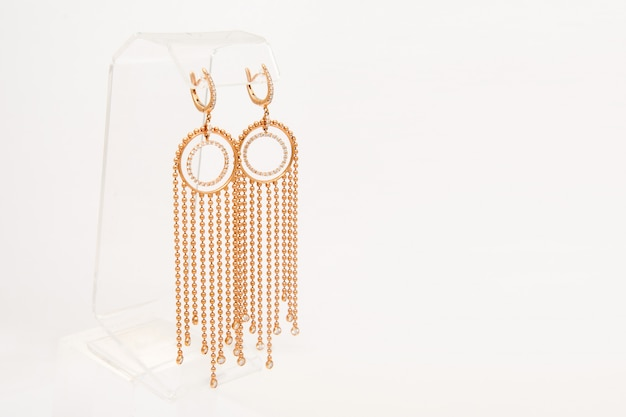 Golden earrings with diamonds on white