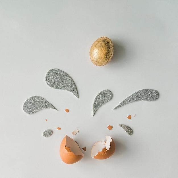 Золотое пасхальное яйцо с серебряными и золотыми блестящими вкраплениями на белой поверхности
