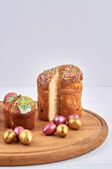 Золотые пасхальные яйца и вкусный пасхальный хлеб. традиционная православная христианская пасхальная еда на белом фоне.