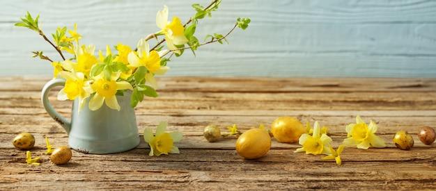 Золотые пасхальные яйца и желтые цветы на деревянных фоне
