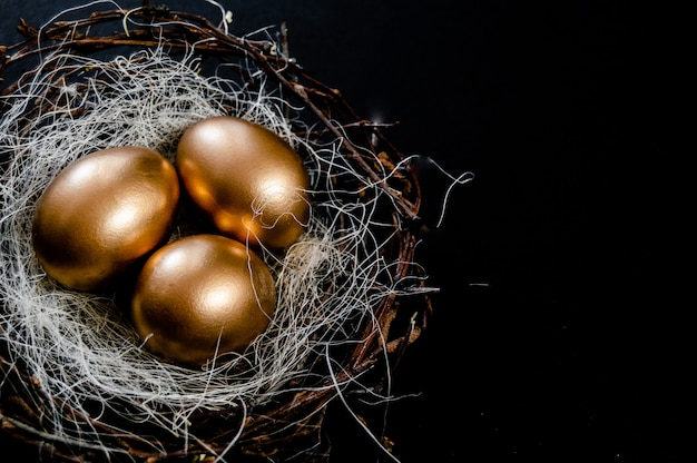 Golden easter eggs in birds nest on black background. easter holiday concept abstract background copyspace top view several objects. close up view