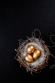 Golden easter eggs in birds nest on black background. easter holiday concept abstract background copyspace top view several objects.