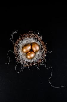 Golden easter eggs in birds nest on black background
