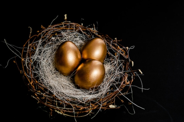 Golden easter eggs in birds nest on black background.