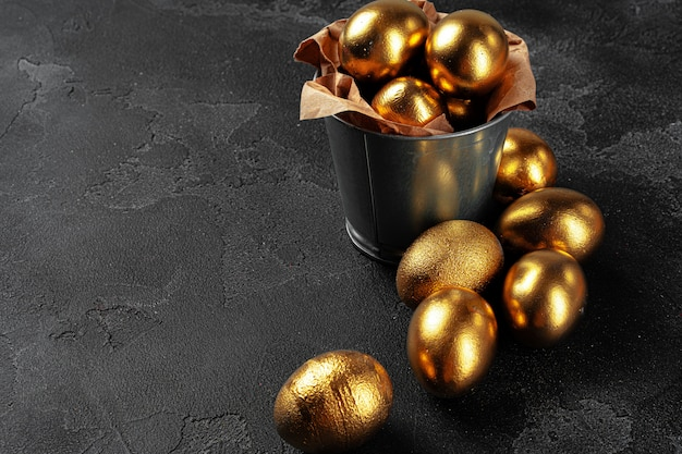 Golden easter eggs on a black concrete background