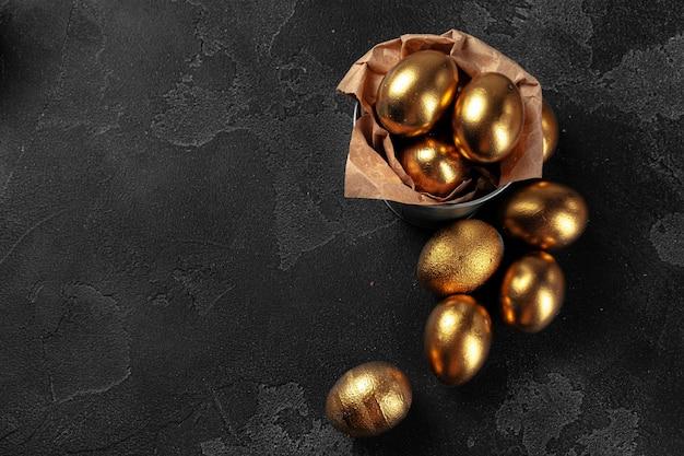 Golden easter eggs on a black concrete surface