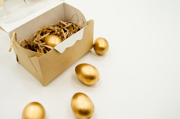 Golden easter eggs in a box with golden stars on white background
