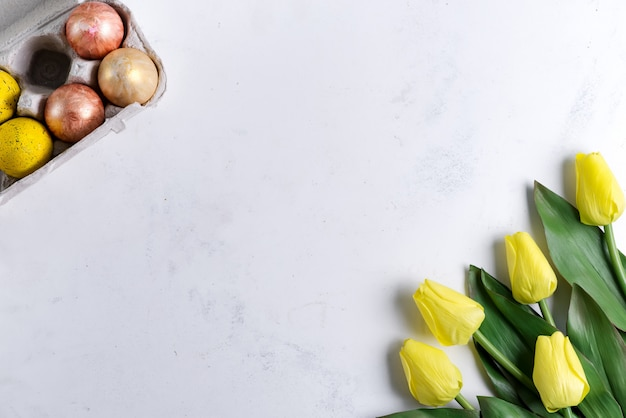 Golden easter eggs in box with yellow tulips on stone marble background. easter background or easter concept.