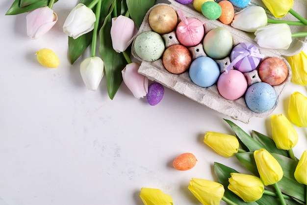 Golden easter eggs in box with yellow tulips on stone marble surface