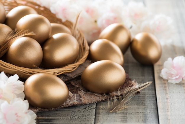 Golden of easter eggs in nest with pink flower and feather