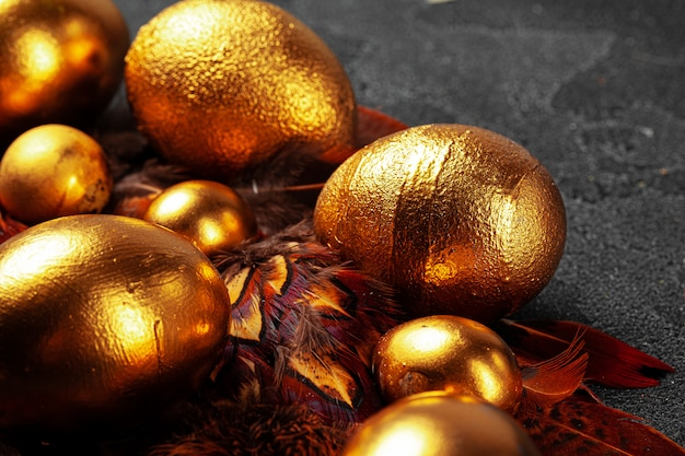 Golden easter eggs on red bird feathers close up