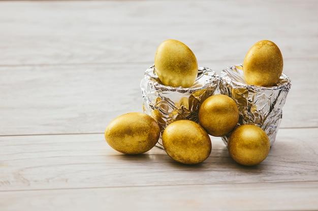木製のテーブルに銀箔のスタンドと黄金のイースターエッグ