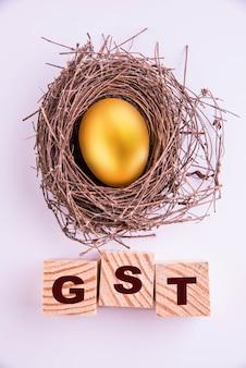 흰색 배경 위에 격리된 나무 큐브에 쓰여진 황금 달걀과 gst 단어, 선택적 초점