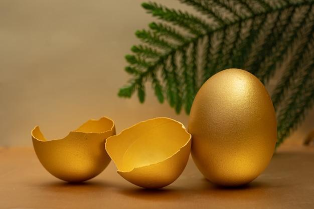 황금 계란과 황금에 노른자와 절반 깨진 계란