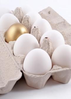 흰색 배경에 있는 판지 상자에 있는 황금 달걀과 재스트 달걀