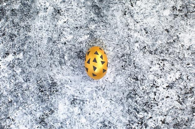Golden egg in black triangles