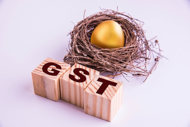 Golden egg and gst word written on wooden cube, isolated over white background, selective focus
