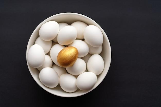 황금 알은 검은 배경에 그릇에 흰색 것들 위에 있습니다.