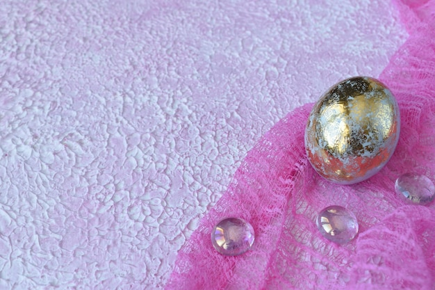 Golden egg on a pink background with glass pebbles