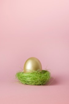 Golden egg in pink nest. easter minimal creative composition on pastel pink with copy space. close up. happy easter holiday. greeting card.