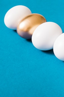 Golden egg standing out from white eggs on blue background